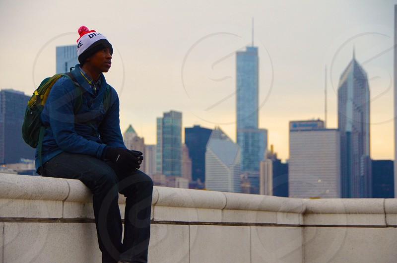 man sitting on white concrete gutter photo