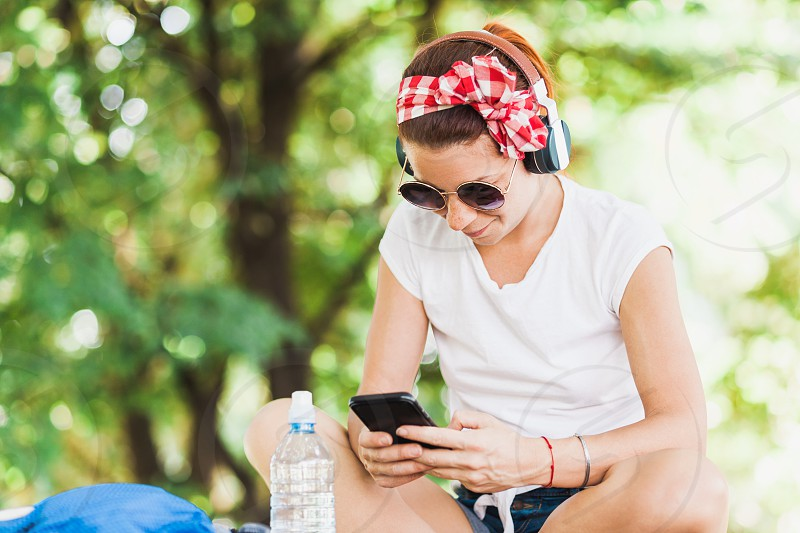 Young woman listening to the music on the smartphone photo