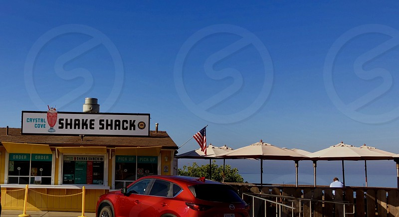 Neighborhood Storefronts Crystal Cove Laguna Beach California Shake Shack Overlooking The Pacific Ocean With Umbrellas photo