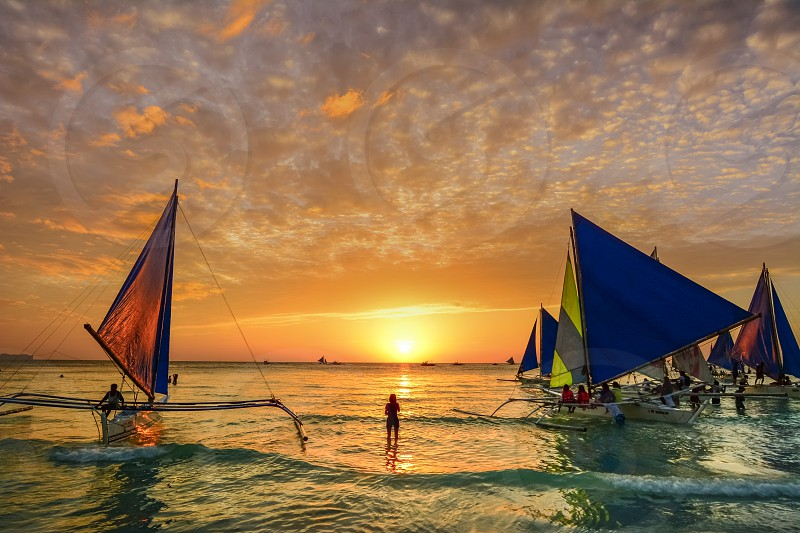 People admire the scenic sunset from the typical filipino boats photo