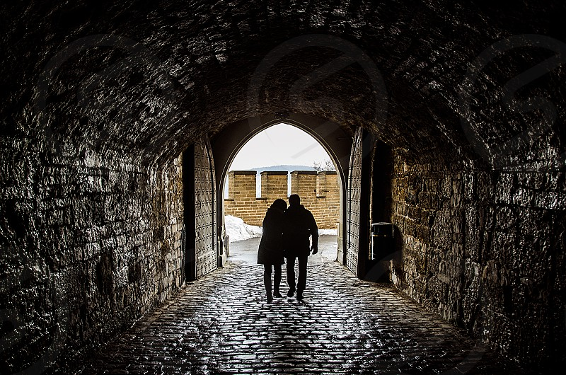 couple love archway silhouette shadow walking europe winter cold photo