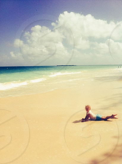 child lying on her stomach on the beach photo