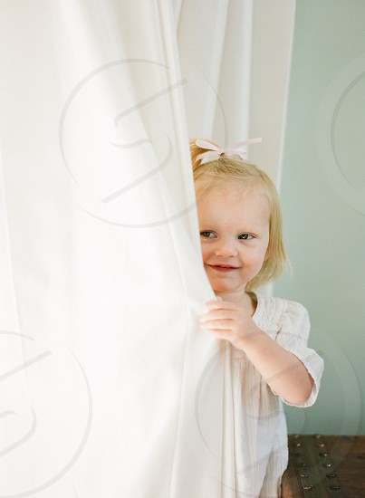 Toddler girl hiding peek a boo hair ribbon white photo