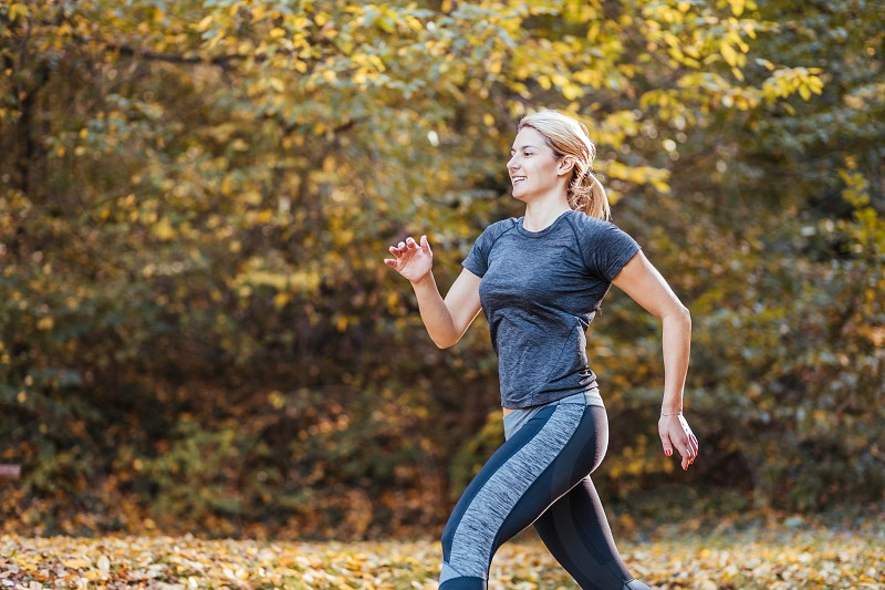 Young sporty woman running in the woods in autumn photo