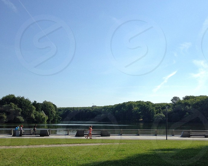 2 women running on park near body of water under blue and white sunny cloudy sky photo
