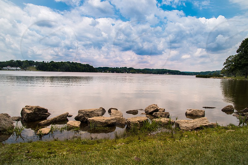 Wide shot of a lake to show everything surrounding and beautiful sky.  photo