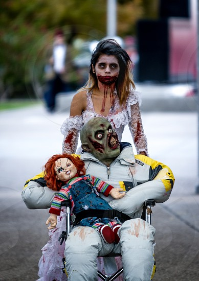 photography of couples with zombie costume and chuckie doll during daytime photo