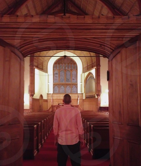 man in pink long sleeved collared shirt looking at the church room photo