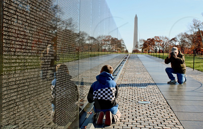 Grandfather photographs his grandson near The Vietnam Veteran's Memorial: The Wall. The Washington Monument is seen in the background. photo
