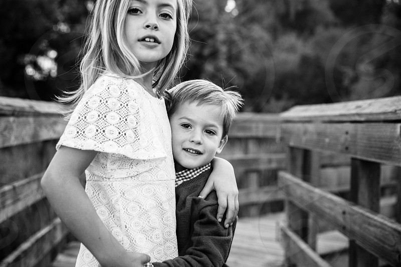 blonde girl in a white dress with her arm around a younger boy standing on a wood path with rail grayscale photo photo