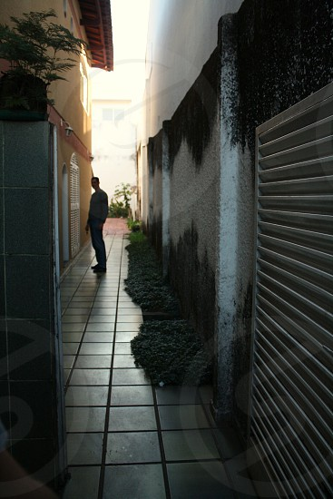 silhouette of man standing on gray tile pathway between white and yellow concrete buildings photo