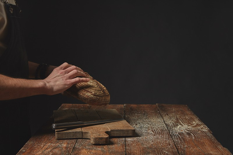 On a dark background hands of a man holding a round bread photo