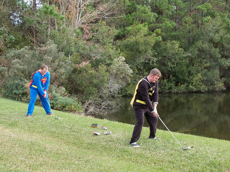 Brothers competing golf swings while in their superhero pajamas photo
