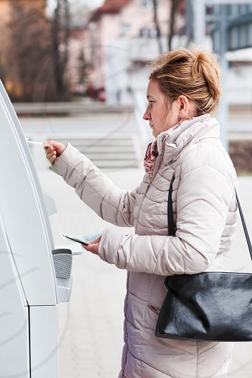 Woman drawing out money from ATM photo