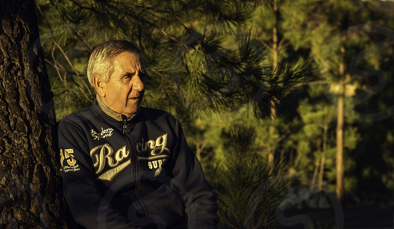 Handsome senior man with sportwear resting on a tree at the woodland  and looking afar with copy space photo