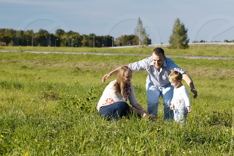 Protective father playing with his wife and son in a grassy field in open countryside as they laugh and frolic enjoying the fresh air and sunshine photo