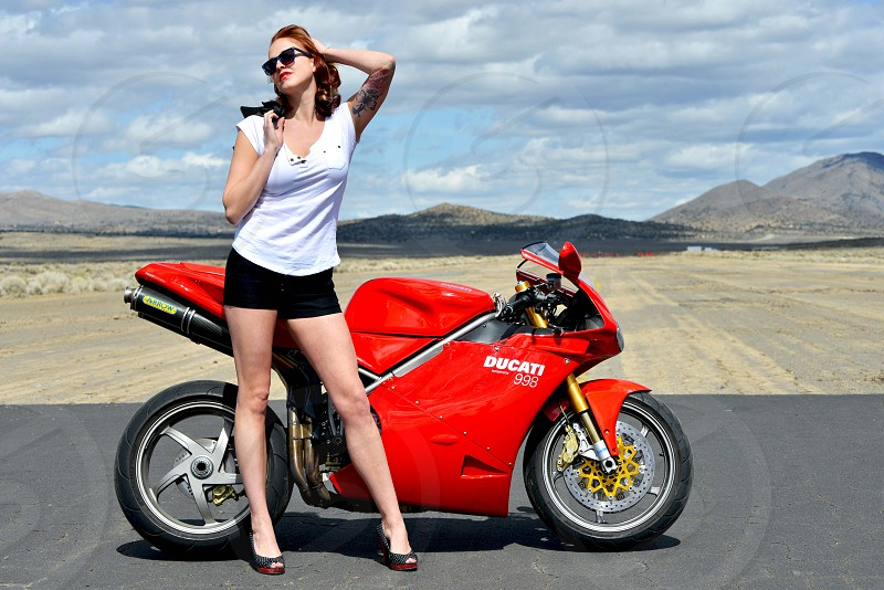 woman in white tank top standing beside red ducati motorcycle under white cloudy sky during daytime photo