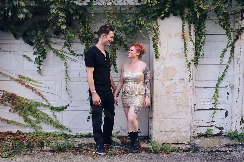 man and woman standing near vine overgrown garage door photo