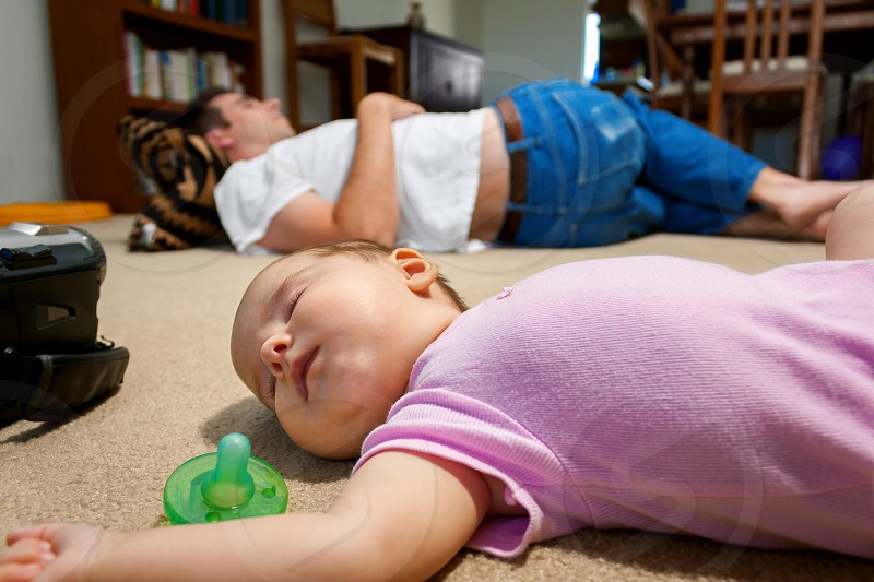 A newborn baby and her father lay sleeping on a family room floor.  The exhaustion of having a new baby has set in. photo