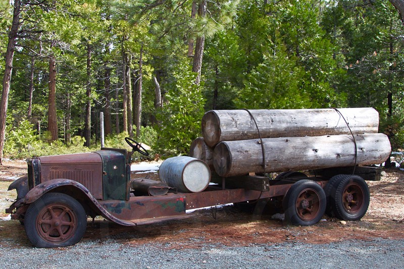 Antique logging truck logs strapped to back end photo