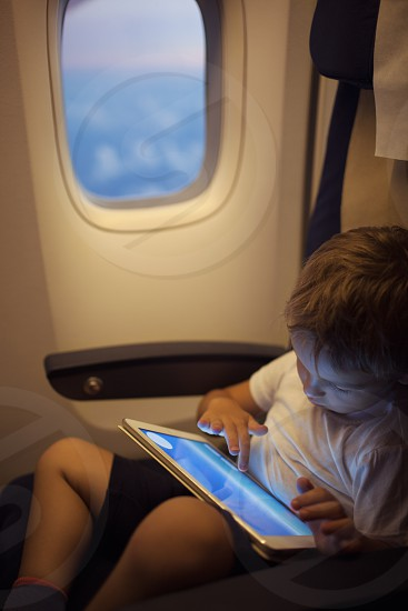 Little boy in the plane sitting by the illuminator and using touch pad to entertain himself photo
