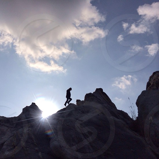 silhouette of person walking up rocky mountain area at sunrise photo