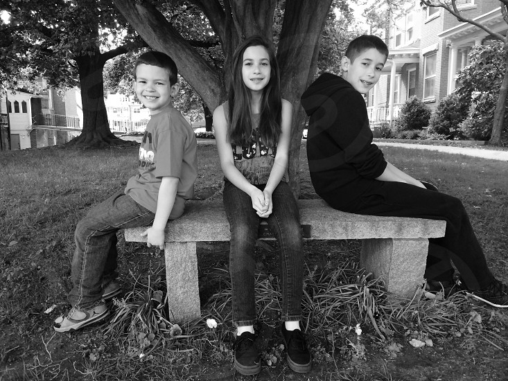 2 boys and 1 girl sitting on park bench photo