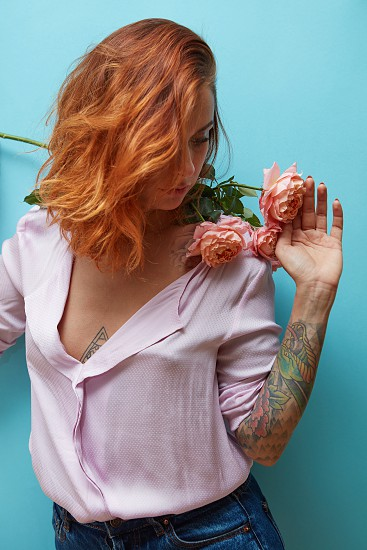 Beautiful young woman with red hair and tattoo on her hand holds fresh roses on the shoulders on a blue background. Place for text. Postcard on Mother's day photo
