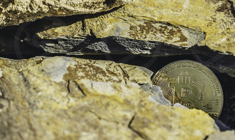 Golden bitcoin coin stuck between stones. Cryptocurrency mining concept selective focus photo