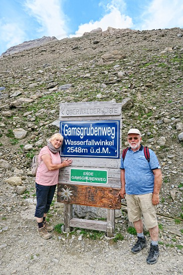 Grossglockner SALZBURGER LAND/ AUSTRIA July 30 2016: hiker walking along a path at Grossglockner Mountain and Pasterze in Austria. Posing in front of information sign Gamsgrubenweg trail. photo