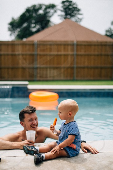 man on swimming pool holding white cup while watching the boy wearing blue and black onesie during daytime photo