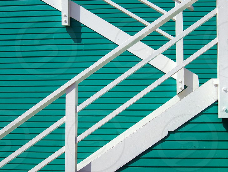Seen from the side a white wooden staircase becomes abstract art against an aqua wall. photo