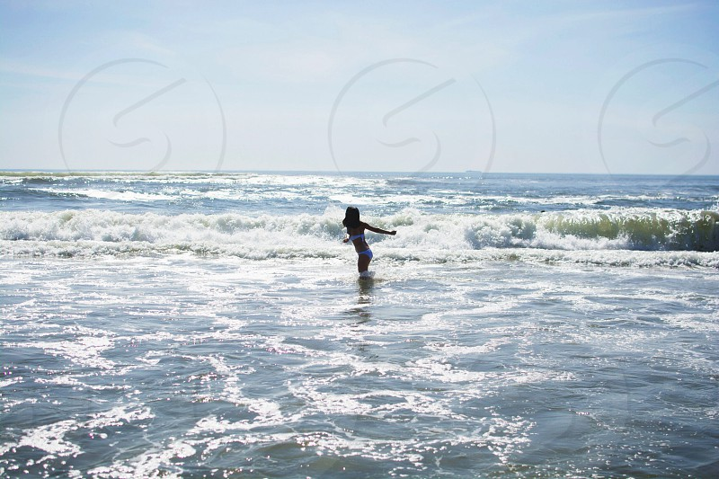 woman in the middle of beach waves photo