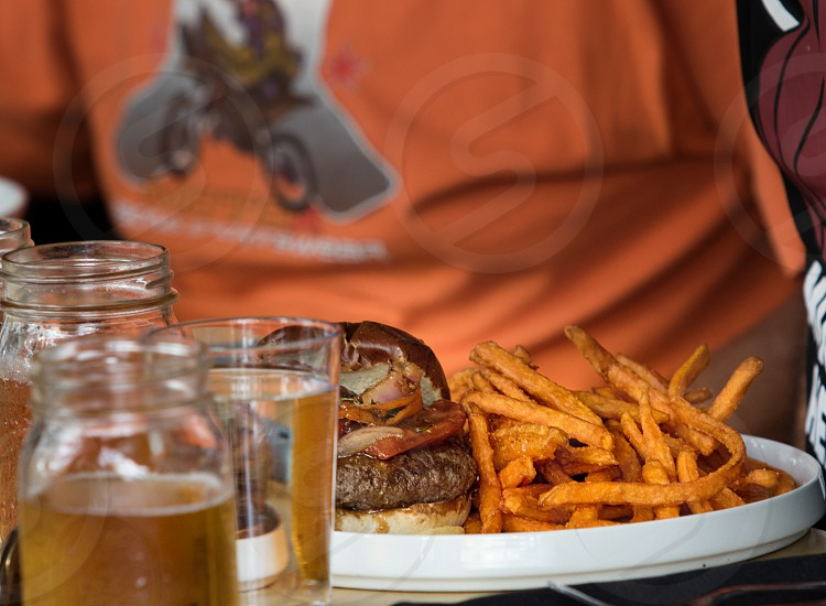 meat burger beside french fries on white ceramic dish photo