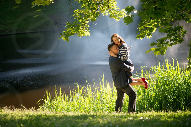 Romantic couple in love walking and kissing in city park photo