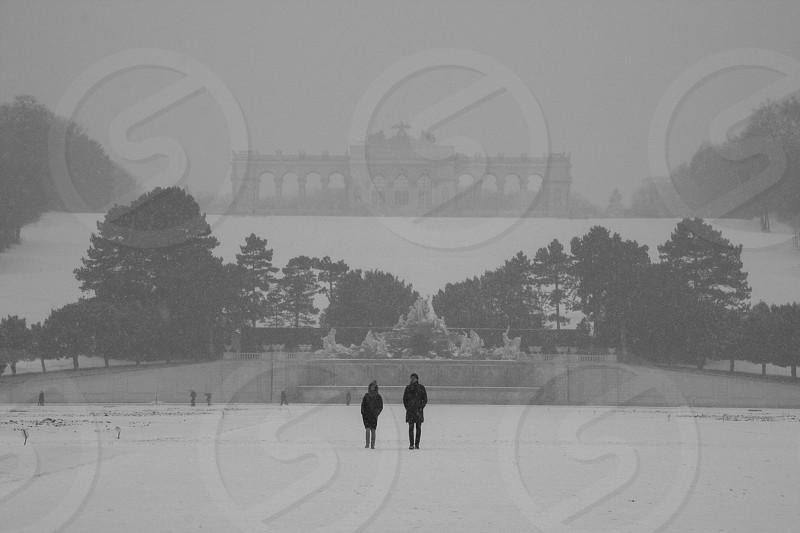 man wearing black jacket walking on snow photo