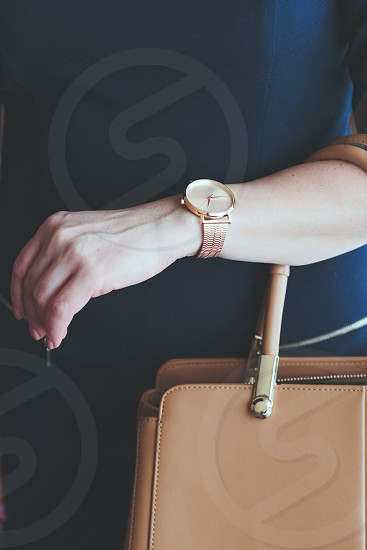 Elegant woman wearing pink gold wristwatch with bracelet and blue dress holding leather handbag photo