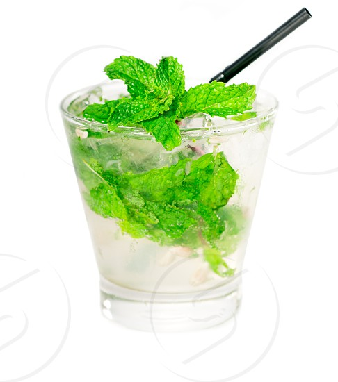 mojito caipirina cocktail with fresh mint leaves yerba-buena with lime and black straw isolated on white background photo