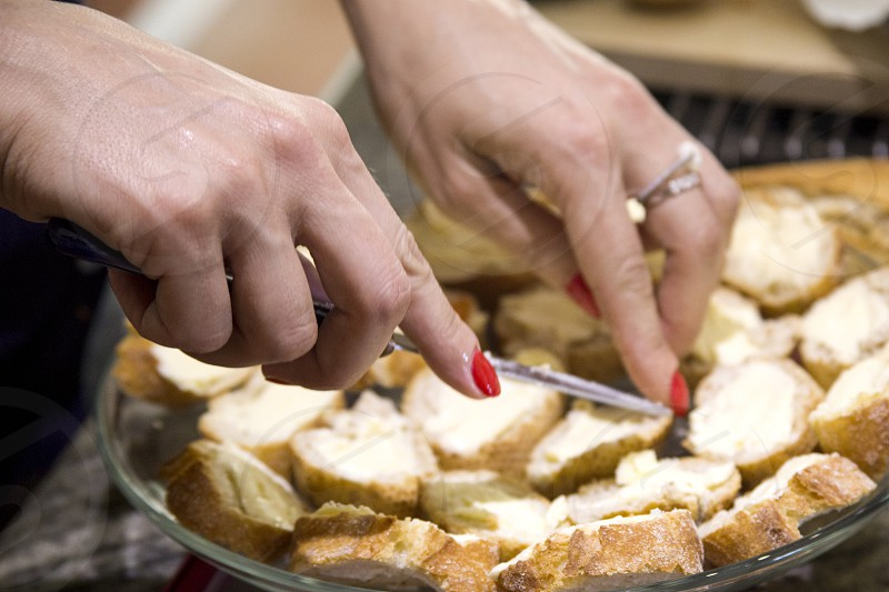 The girl makes sandwiches with fresh bread and butter. photo