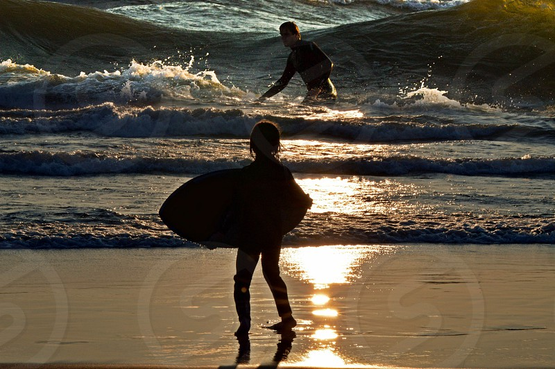 silhouette of two surfers in Lake Michigan surfing summer exercise photo