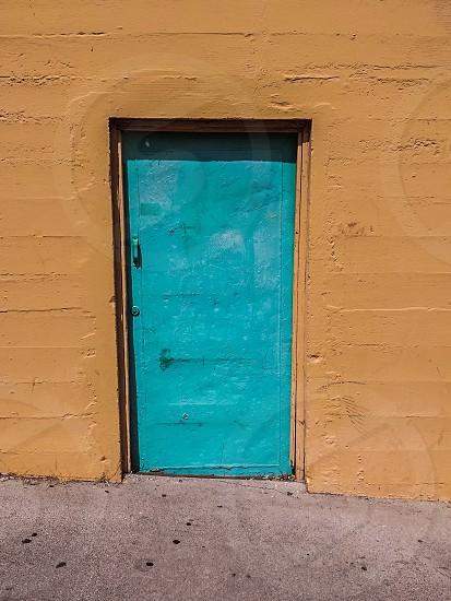 closed teal door on mustard brown painted building photo