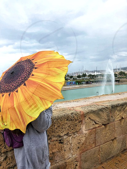 A beautiful young girl is standing on a rainy day under an yellow umbrella in the form of a sunflower near an ancient stone fence against the background of a pond with a fountain and a sea port  photo