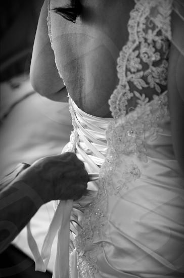 Wedding dress getting put on. Black and white  photo