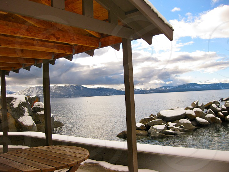 Wooden outdoor seating overlooking snow covered rocks during winter in Lake Tahoe photo