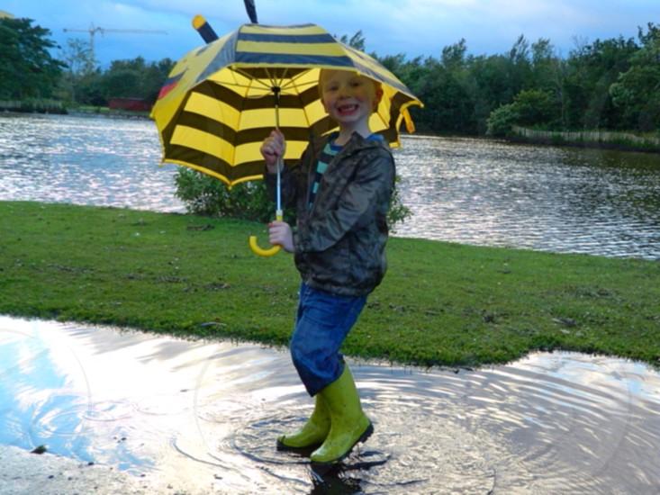 kid holding yellow and black stripe umbrella photo