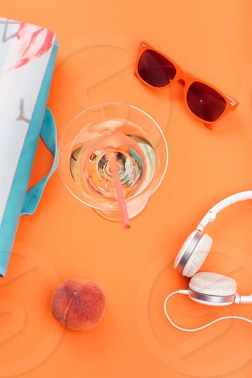 Sunglasses glass with drink headphones peach blanket on orange background. Minimal summer style photo