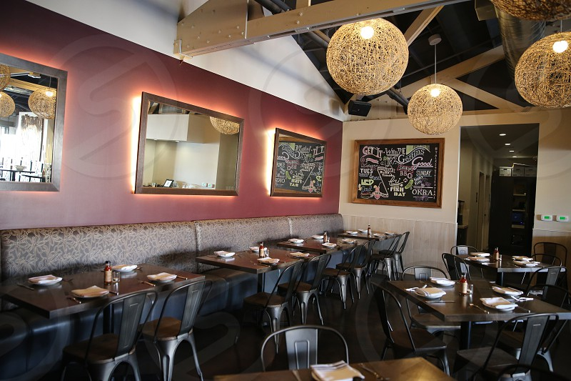 black wooden tables and chairs inside restaurant with framed mirrors on walls and brown round pendant lamps photo