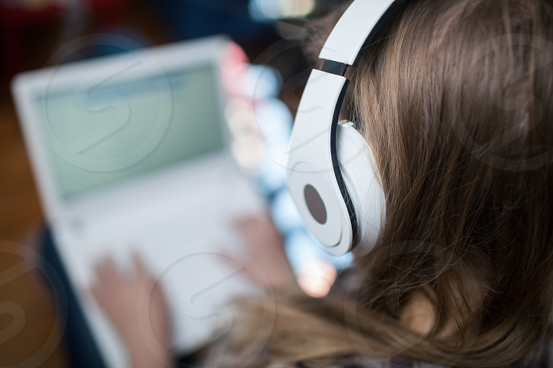 Close-up back shot of woman enjoying music in wireless headphones while typing on laptop. Focus on the girl photo