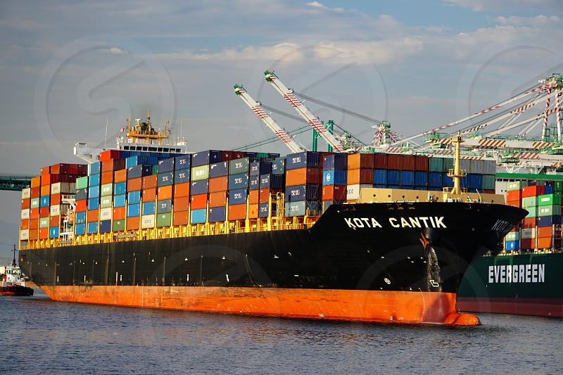 Loaded container ship Kota Cantik in main channel of Port of Los Angeles San Pedro California passing other berths with ships being loaded by gantry cranes. photo