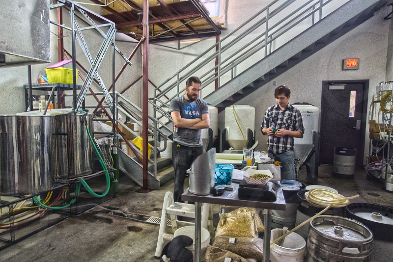 Bunsenbrewer owner and apprentice crafting small batch of beer. photo